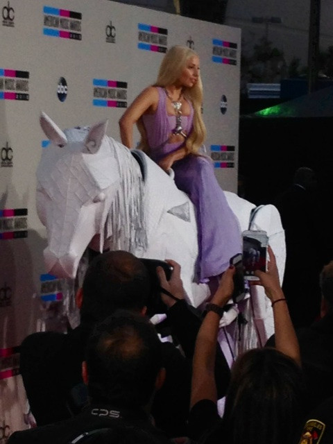 Lady Gaga arrives on a human horse at the 2013 AMA Red Carpet